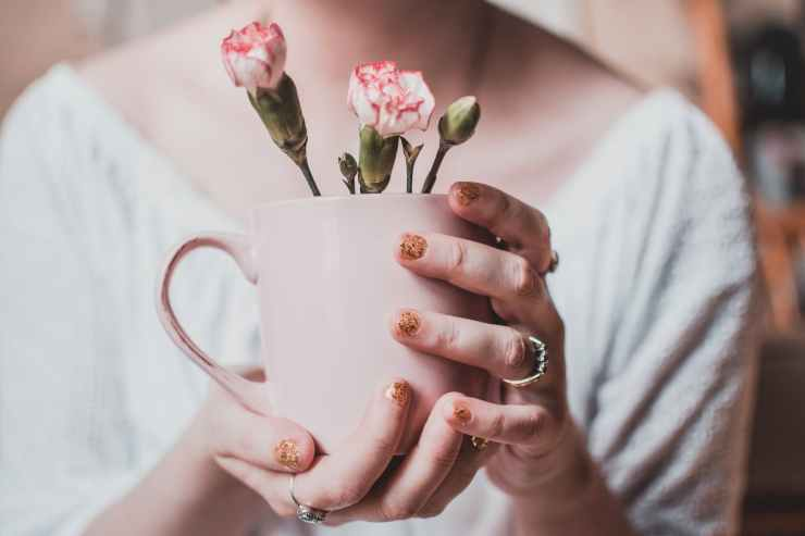 woman wearing white shirt holding pink mug with white petaled flowers