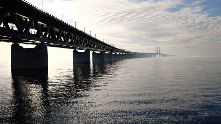 grey concrete bridge on body of water under blue and white sky during daytime