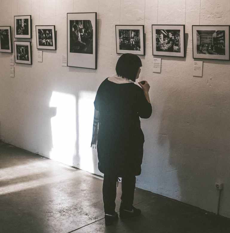 standing woman looking at photos