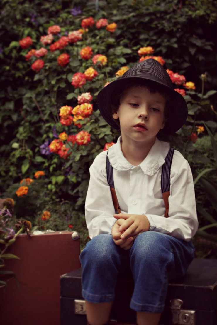 boy wearing black hat sitting on case near flowers
