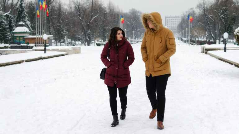 man in brown parka jacket walking beside woman in maroon coat