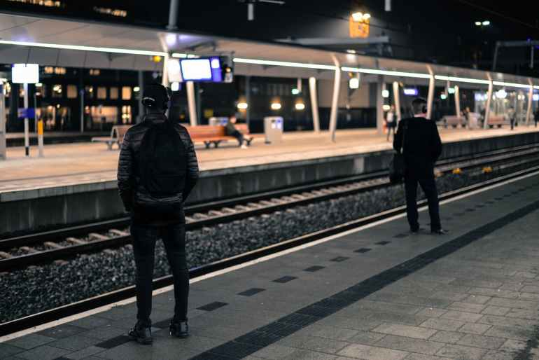 photo of two men standing near railway station
