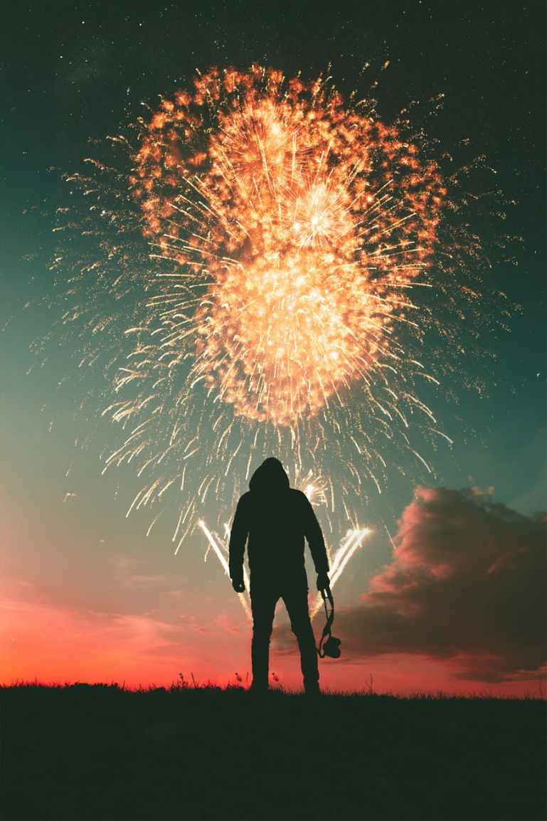 silhouette photo of standing man holding camera looking at fireworks display
