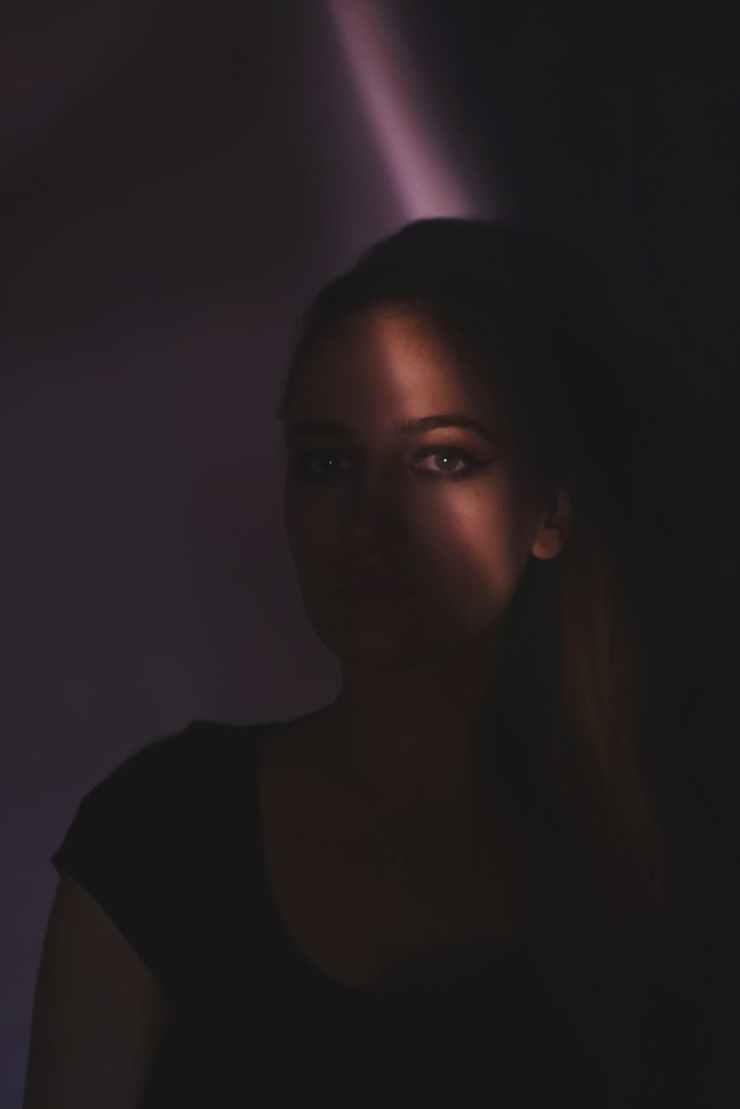 woman in black shirt inside dark room