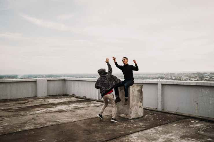 two men going to high five on top of building