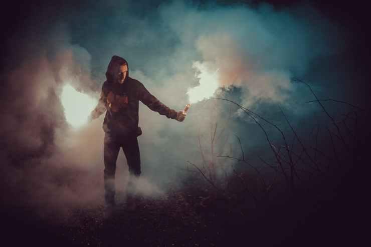 man in black hoodie holding fire