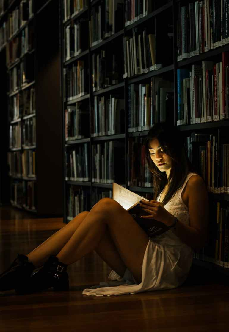 woman leaning on bookshelf