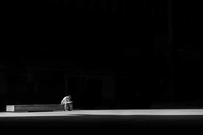man sitting on a concrete bench