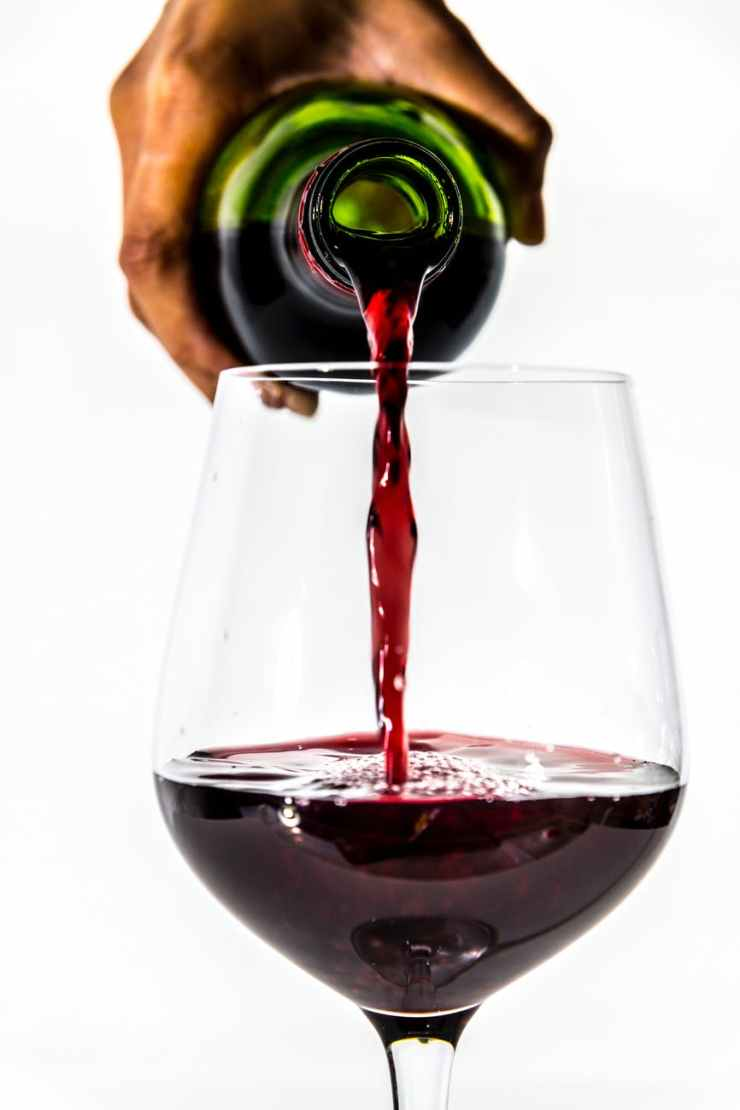 person pouring wine into wine glass