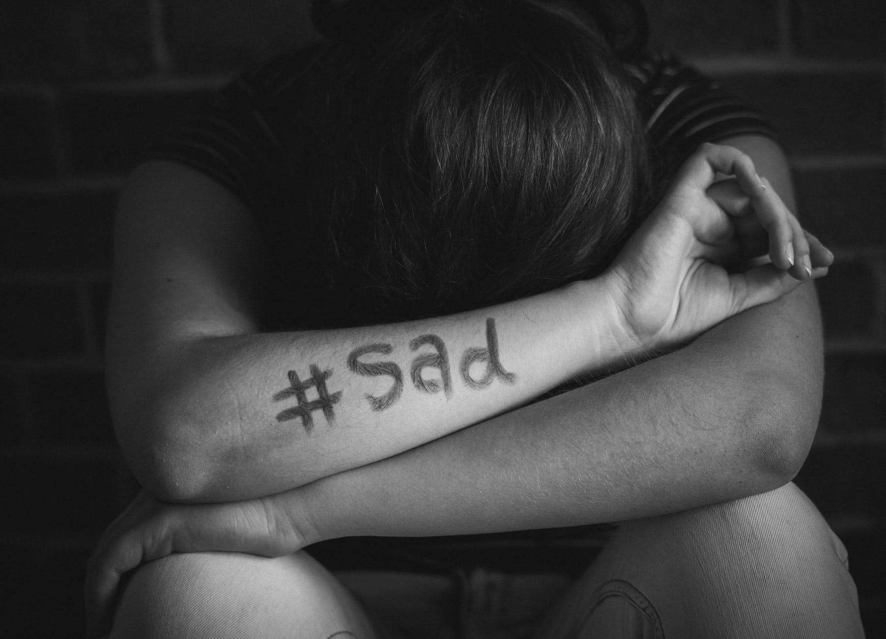 person leans on arms with sad text