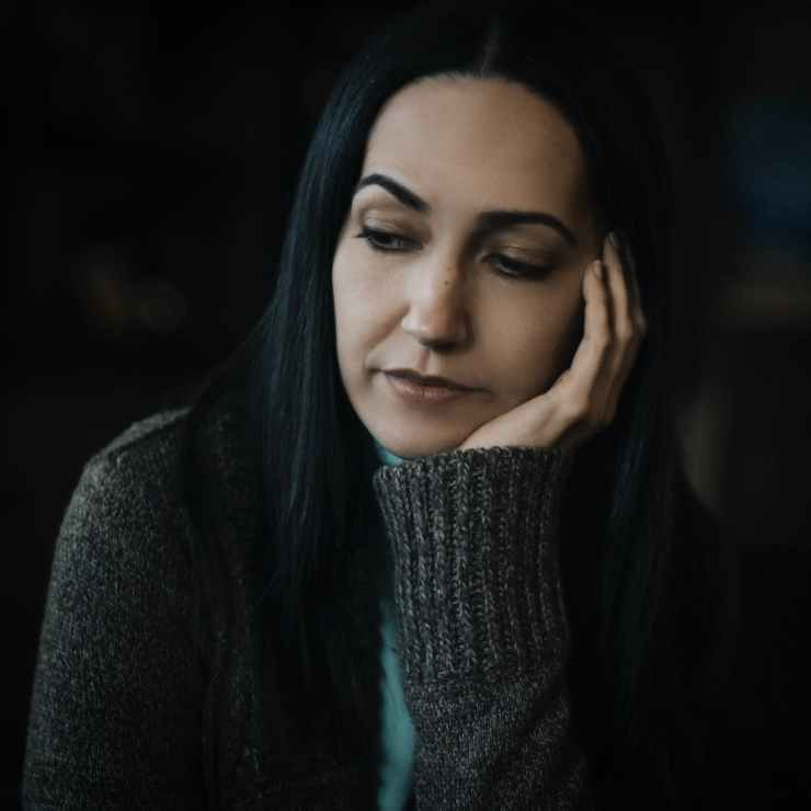 selective focus portrait photo of sad woman in gray sweater with her hand on her cheek