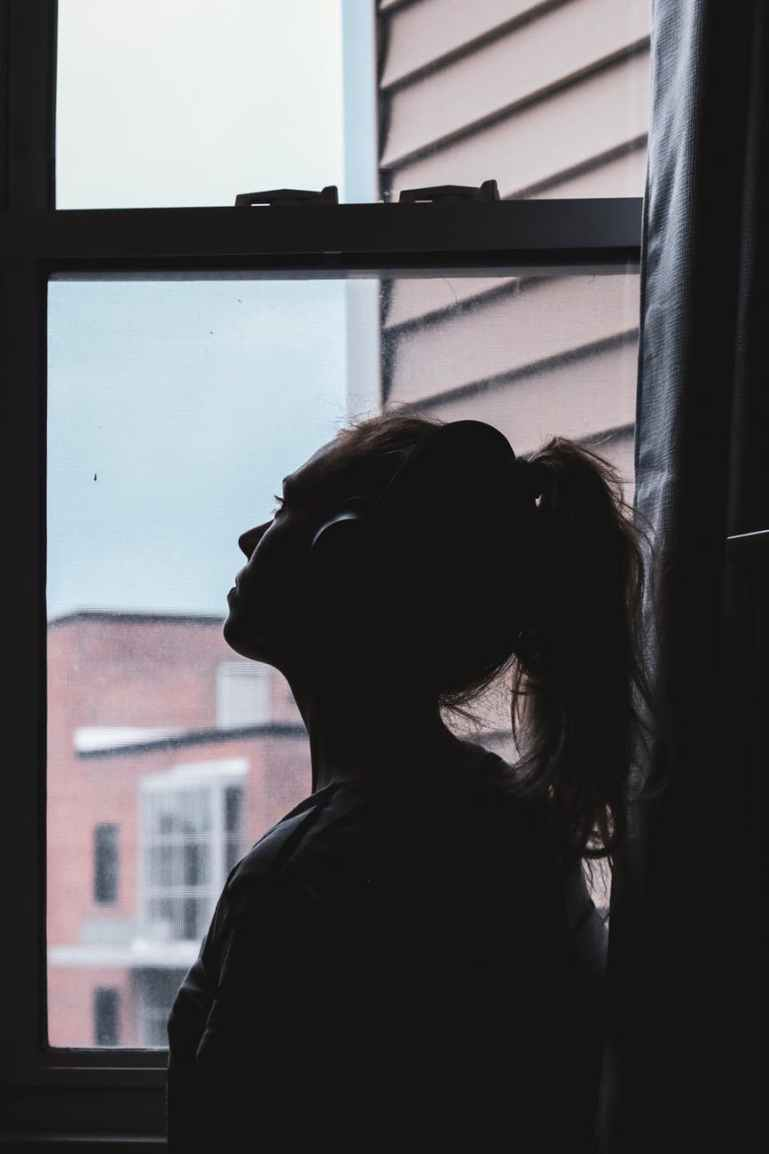 silhouette photo of a woman looking through window