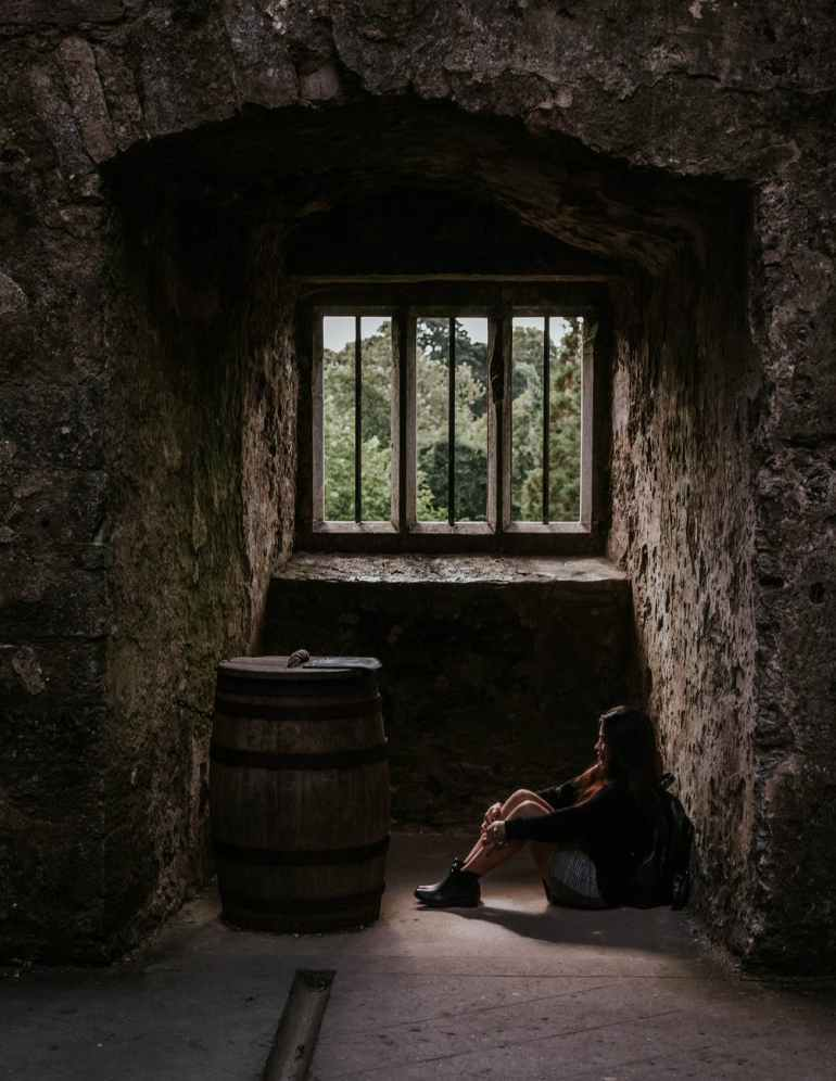 photo of woman sitting down next to barrel