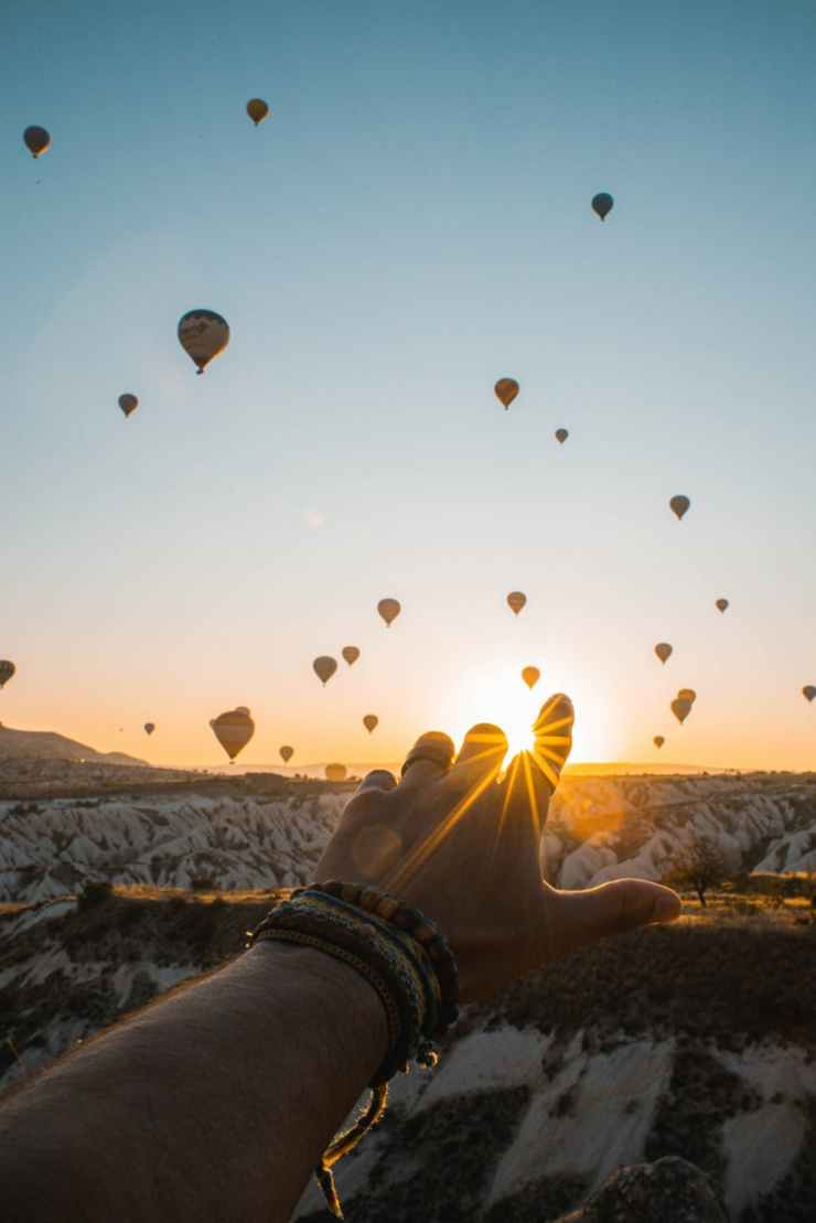 photo of person s hand across flying hot air balloons
