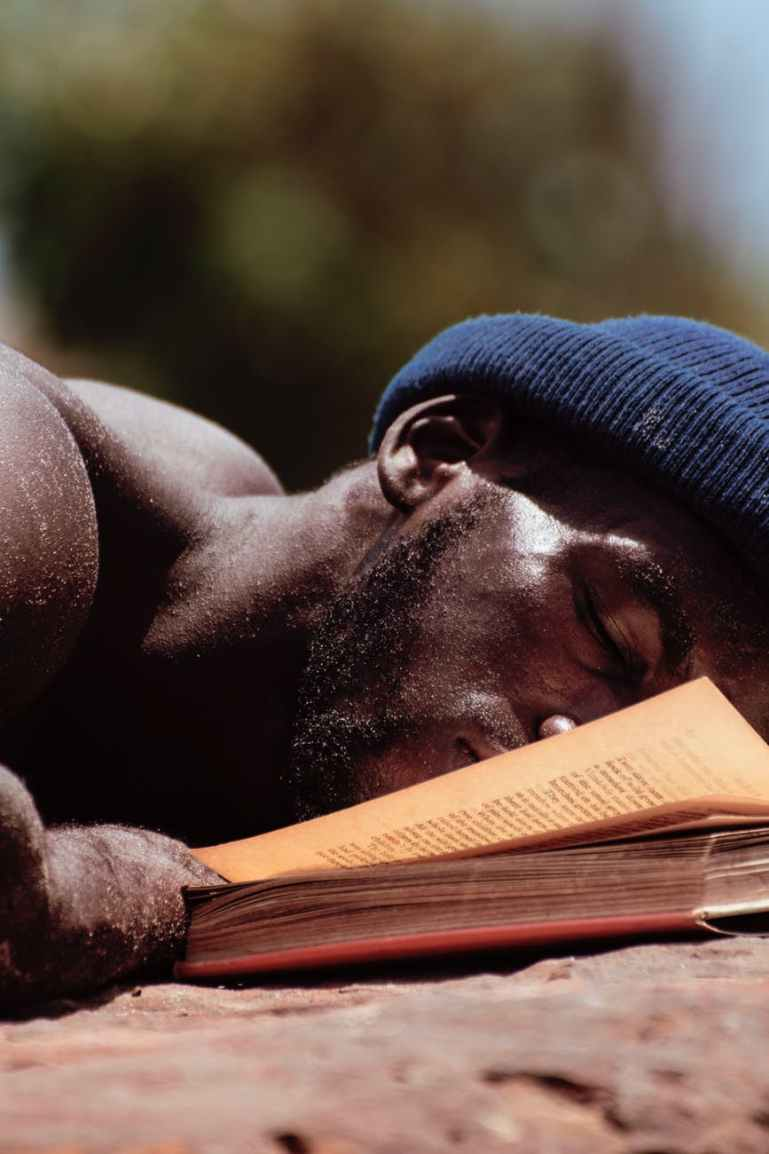 man lying beside a book