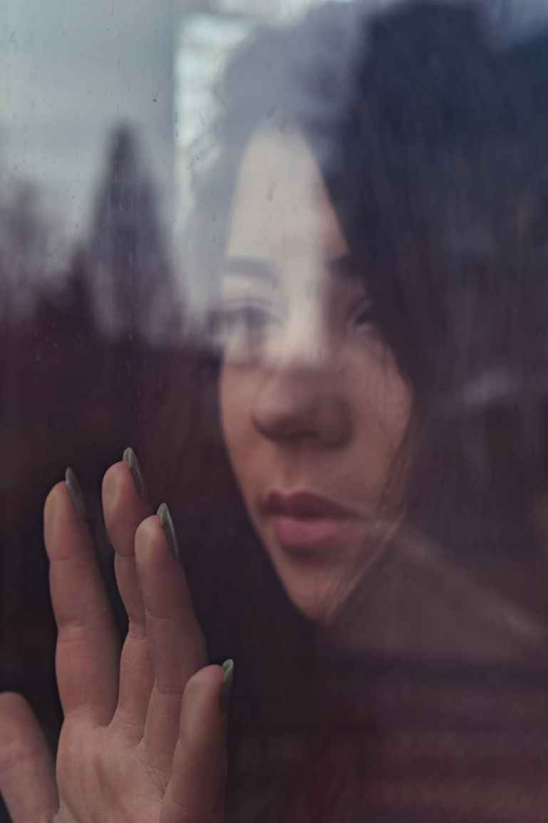 shallow focus photo of woman touching window