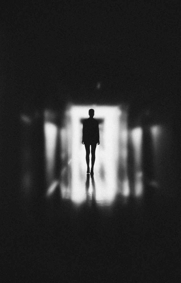monochrome photo of person standing on hallway