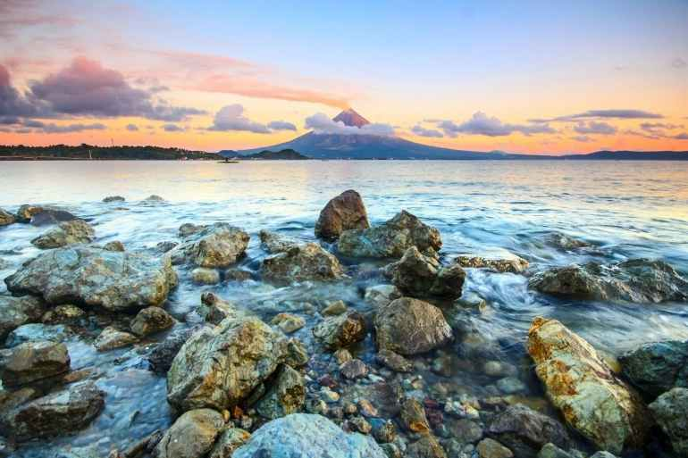 brown and gray rocks on seashore during sunset