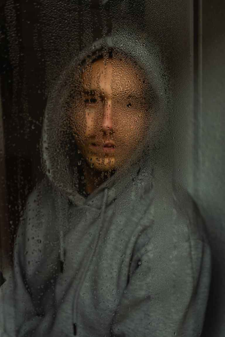 man in gray hoodie behind the window