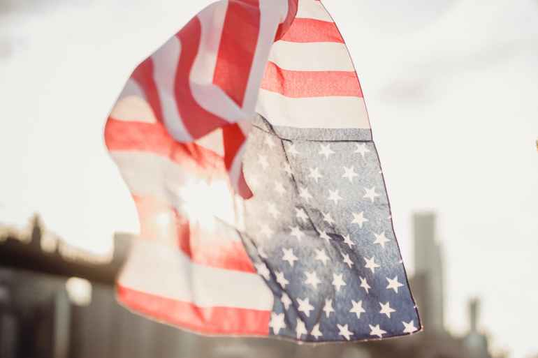 american flag kerchief waving in wind against blurred modern city
