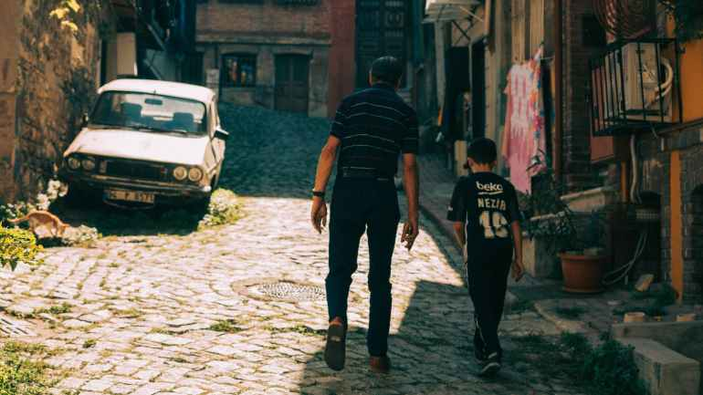 father and son walking on the street